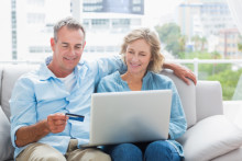 Couple using a laptop on the couch